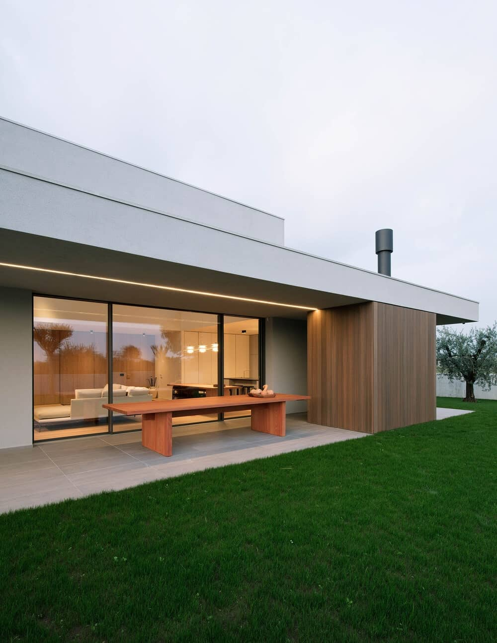 The covered patio of the house right outside the glass wall has a long wooden rectangular dining table.