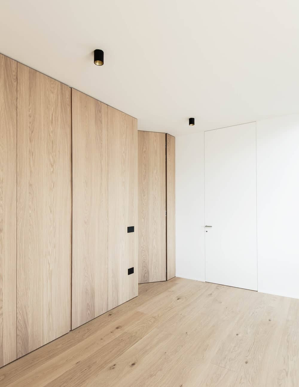 This is a closer look at the wooden panels and hardwood flooring of the far corner of the living room as well as the modern lighting above.