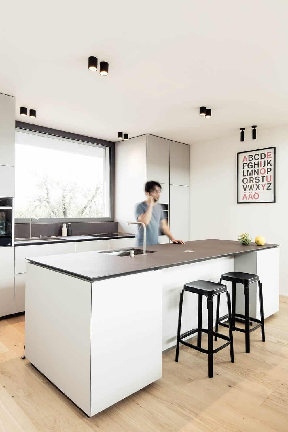 This is the kitchen with a large kitchen island that matches the bright walls that contrast the dark countertops.