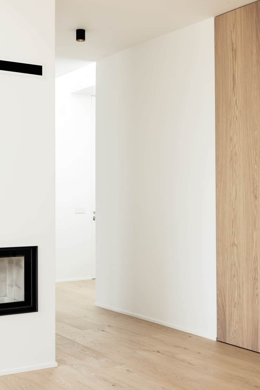 The bright tones of the walls inside the house makes the black stand out that pairs well with the wooden panels and hardwood flooring.