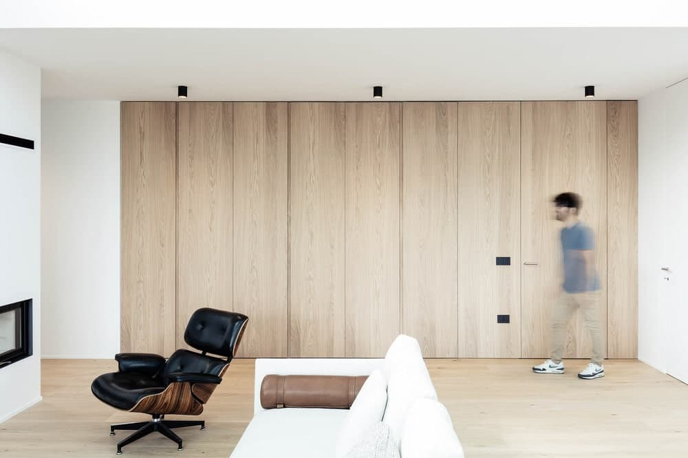At the side of the living room is a wall with wooden panels on it that matches well with the light hardwood flooring.