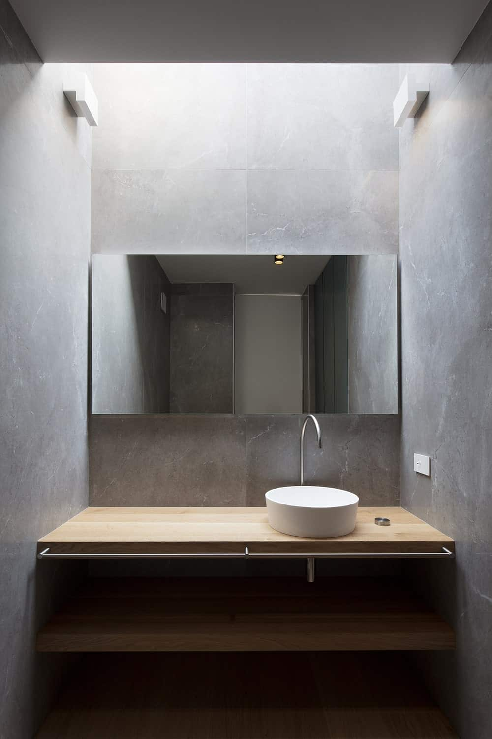 This is the simple wooden vanity of the bathroom with a small circular sink and wooden shelves below the mirror.