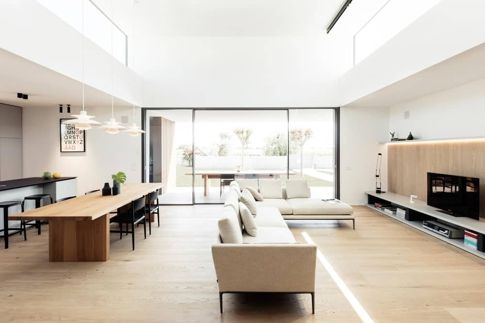 At the back of the L-shaped sectional sofa is the long wooden dining table paired with black chairs that stand out agaisnt the bright ceiling and walls.