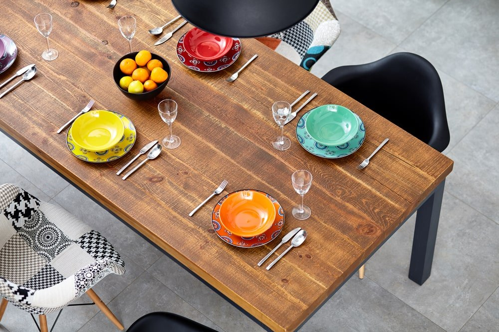 This is a close look at a rectangular dining table with a wooden top surrounded by an assortment of chairs and adorned with colorful dishes.