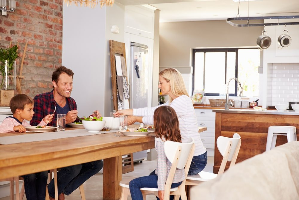 A family of four eating a meal on their wooden dining table by the kitchen island.