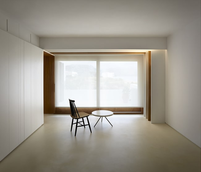 This is a close look at the open minimalist great room of the house with white walls, white ceiling and white built-in cabinets brightened by the natural lighting.