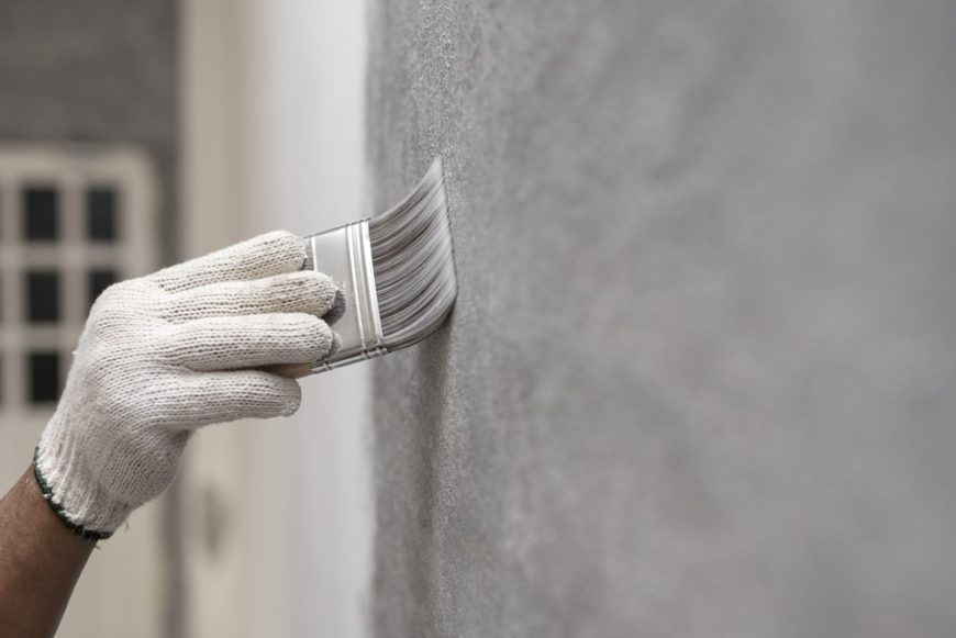 This is a close look at a gloved hand covering a wall with flat paint.