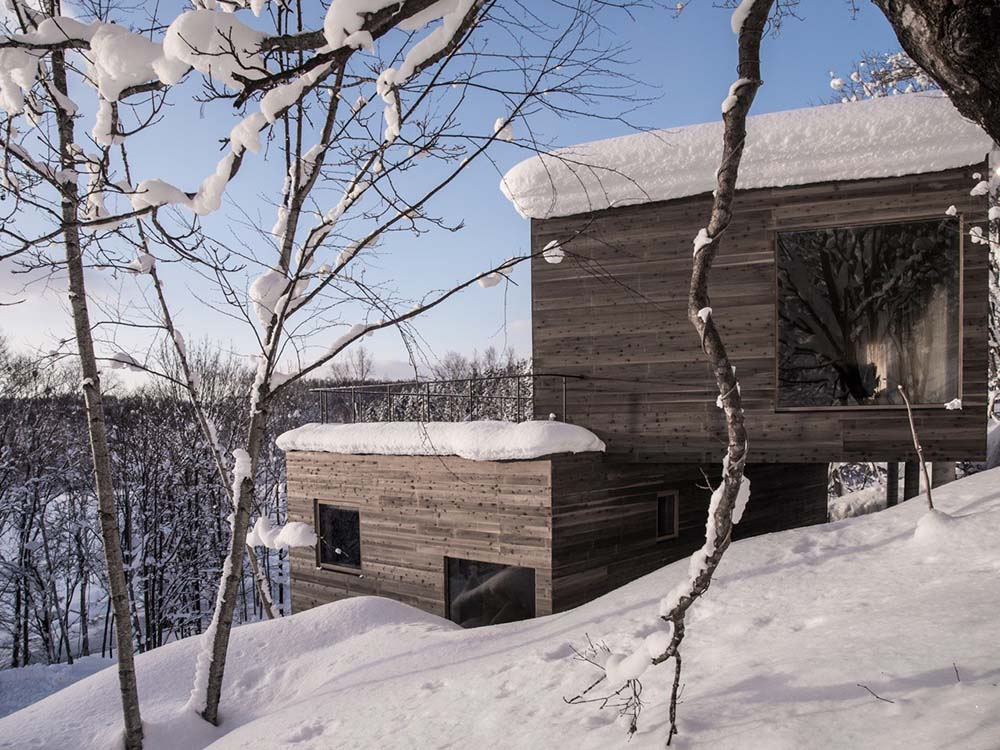 This is a view of the side of the house with dark brown textured exterior walls that stand out against the snowy landscape. You can also see here the balcony with thin railings.