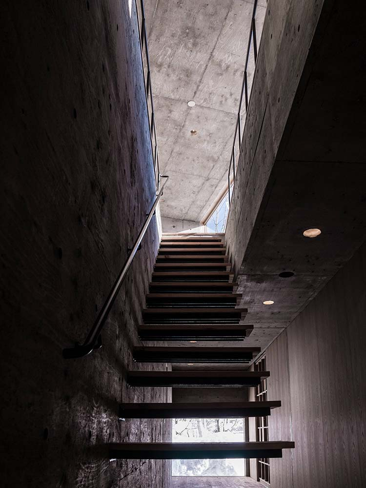 This is another look at the idustrial-style stairs entrance of the house with a view of the concrete tall ceiling.