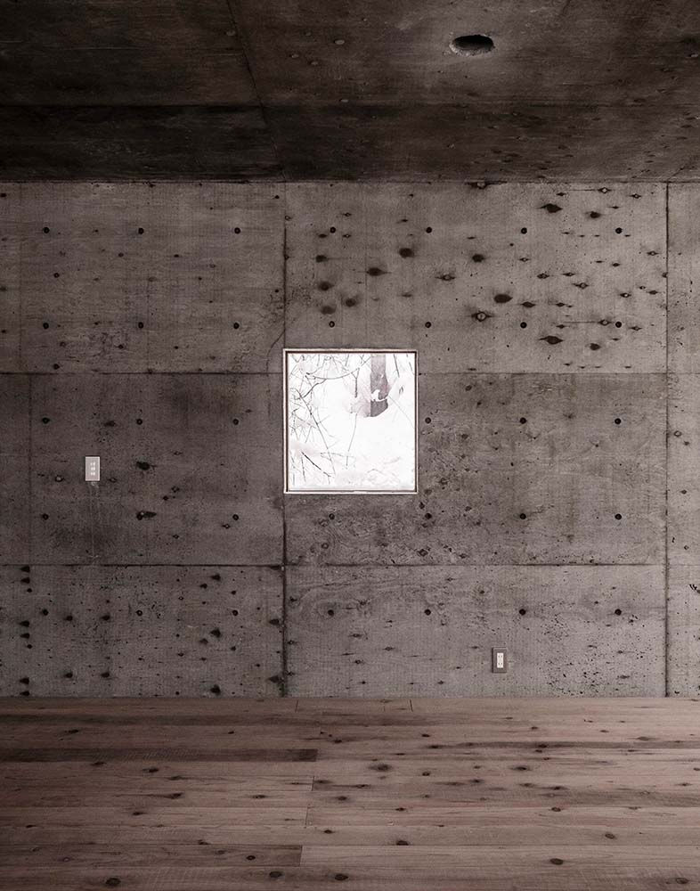 This is a close look at the window that brings in natural lighting to complement the concrete walls and ceiling.