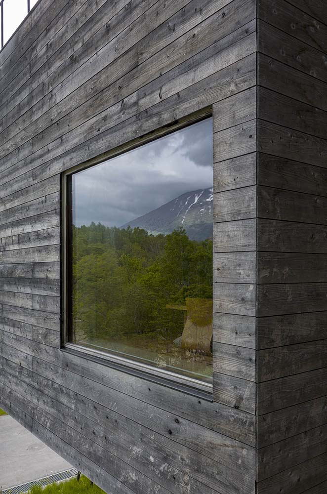 This is a closer look at the exterior of the large glass window complemented by the dark tone of the walls.