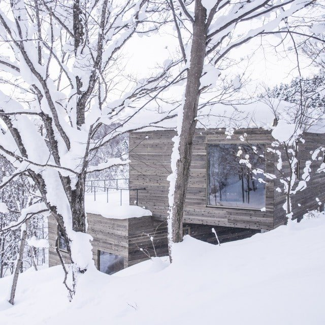 This is a view of the house exterior during winter making the dark exterior walls and windows stand out against the white surroundings.