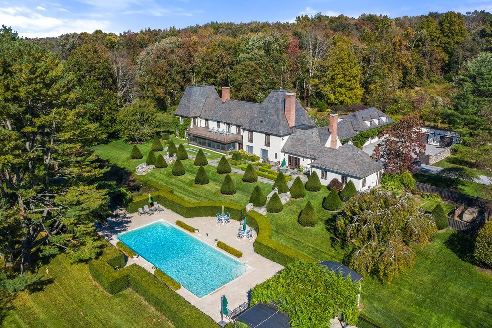 This is an aerial view of the back of the house that showcases the pool area and the lush landscaping that bring color to the neutral tones of the exteriors. Image courtesy of Toptenrealestatedeals.com.
