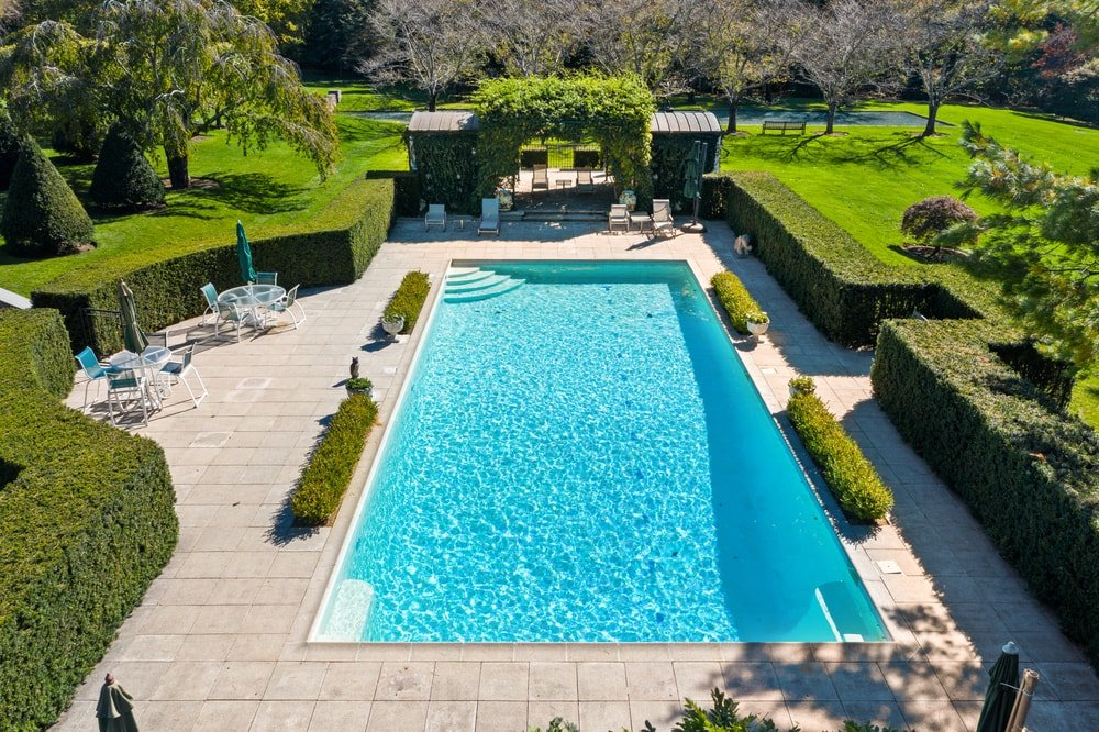 Thisis an aerial view of the swimming pool surrounded by well-manicured shrubs, hedges and bricked walkways. Image courtesy of Toptenrealestatedeals.com.