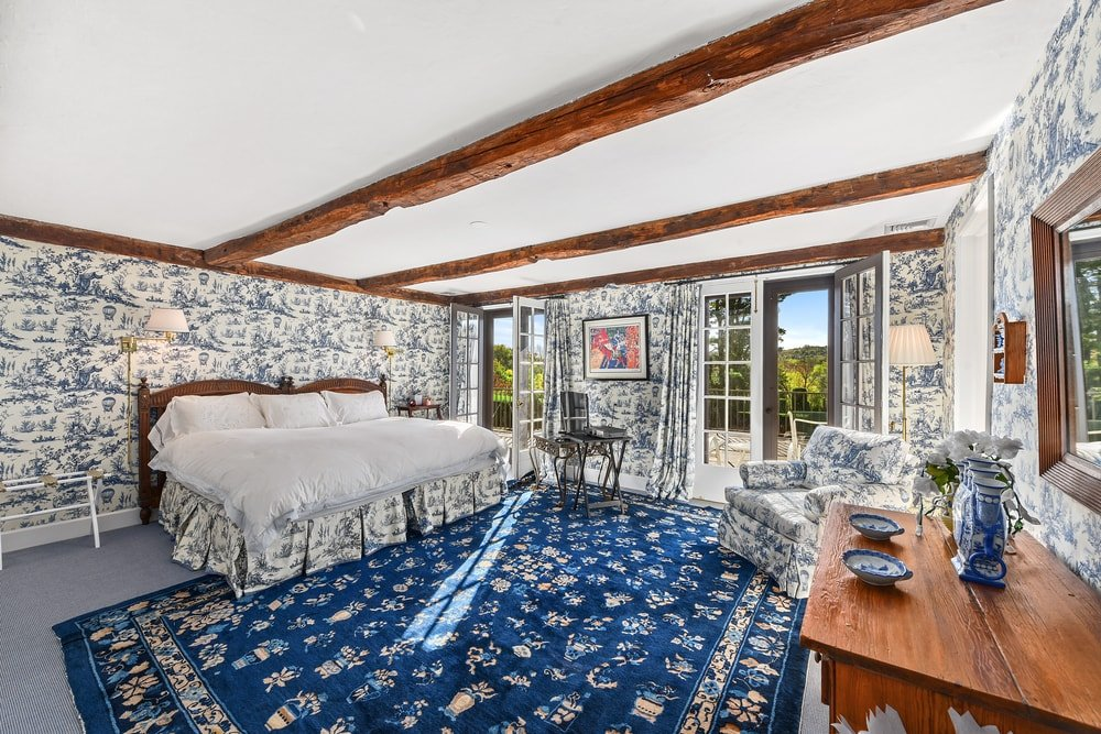 This bed has patterns on its walls and the blue patterned area rug by the foot of the bed that is illuminated by the natural lights of the French glass doors. Image courtesy of Toptenrealestatedeals.com.