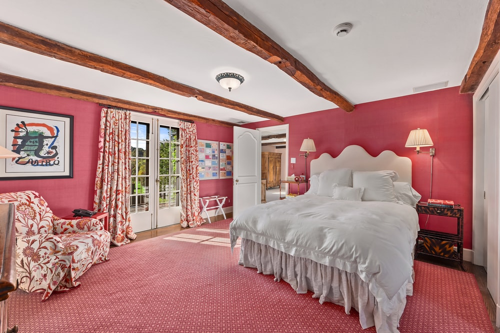 This bedroom has consistent pastel pink tones on its floor and walls that make the bed stand out together with the white ceiling with beams. Image courtesy of Toptenrealestatedeals.com.