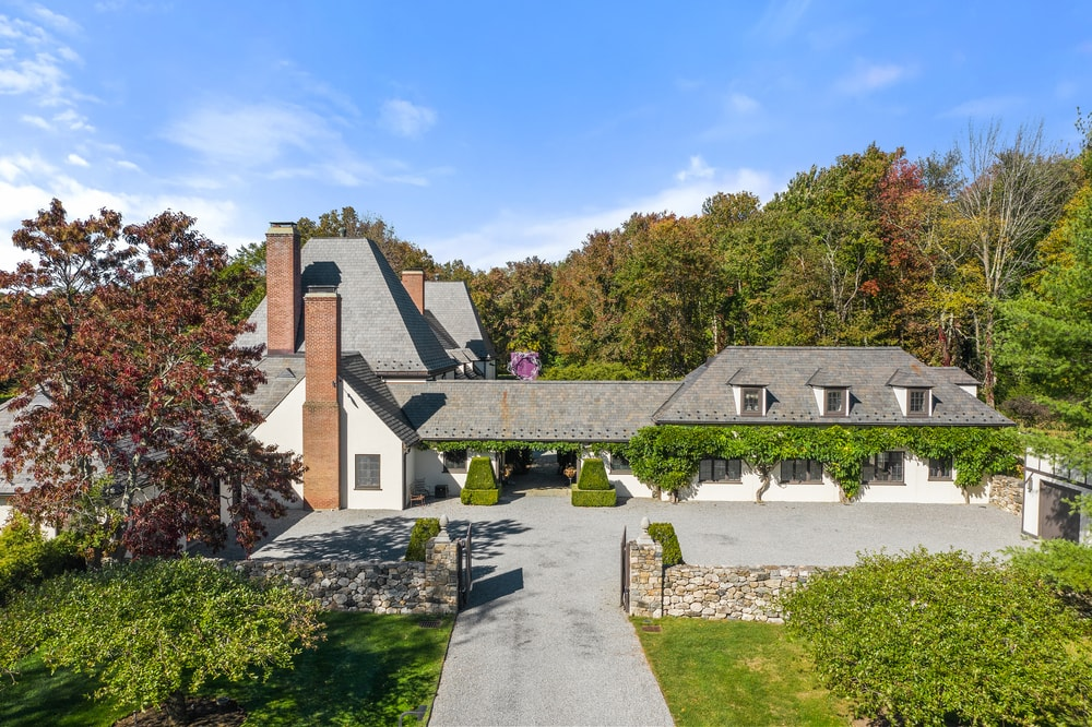 This is a view of the front of the house showcasing a wide driveway, gray roofs with dormer windows and an symmetrical design. Image courtesy of Toptenrealestatedeals.com.