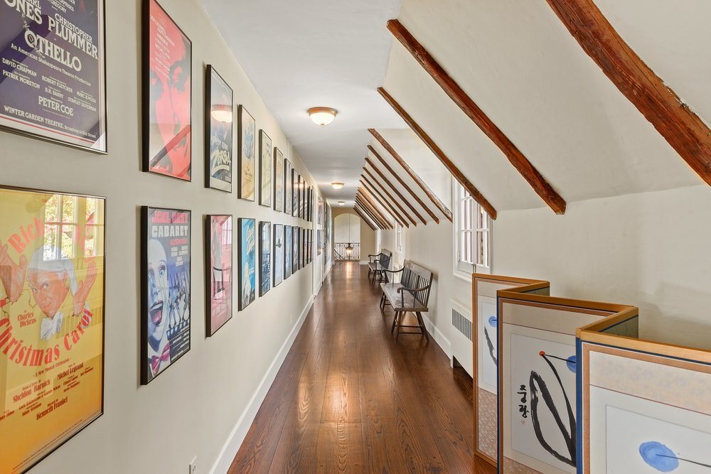 This is a hallway within the house that has a long wall filled with colorful artworks viewed with a bench on the opposite side. Image courtesy of Toptenrealestatedeals.com.