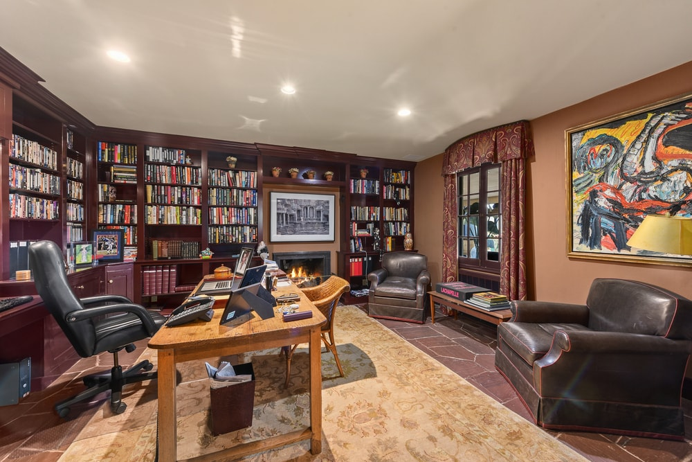This is the home office with a large wooden desk surrounded by dark wooden built-in bookshelves lining the walls. Image courtesy of Toptenrealestatedeals.com.