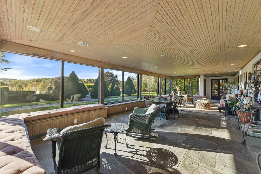 This is the sunroom of the estate with glass walls that bring in an abundance of natural lighting for the dining and sitting areas within. Image courtesy of Toptenrealestatedeals.com.