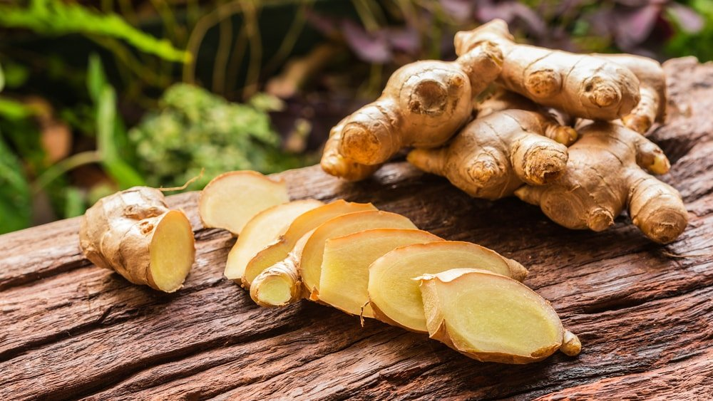 A close look at pieces of ginger root and a few slices of it on a wooden surface.