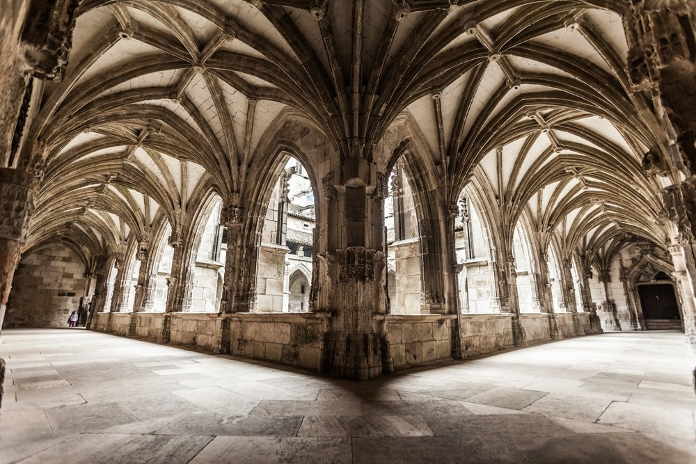 This is a close look at the interior courtyard of a church surrounded by an arched walkway corridor.