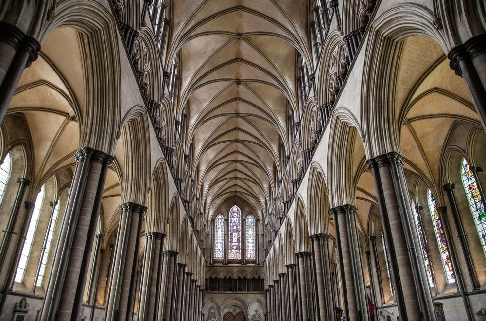 This is a look at the interior of a gothic church with a tall arched ceiling lit by windows.