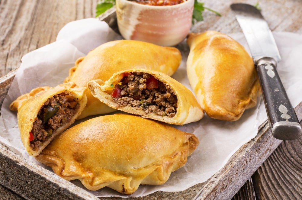 Pieces of beef empanadas on a rustic spread on top of a wooden table.