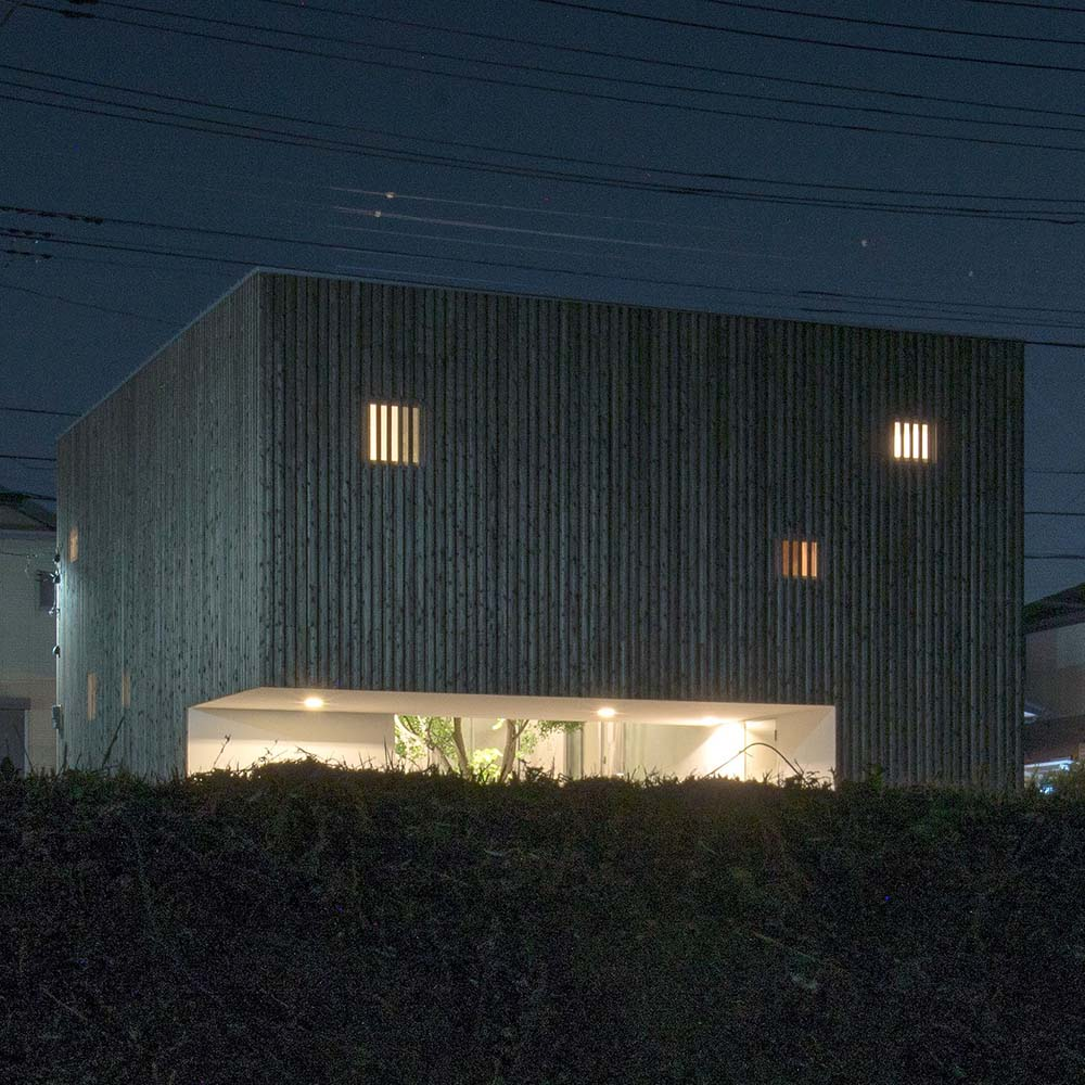 This is a nighttime exterior view of the house that has patterned concrete gray walls and warm glowing windows and openings.