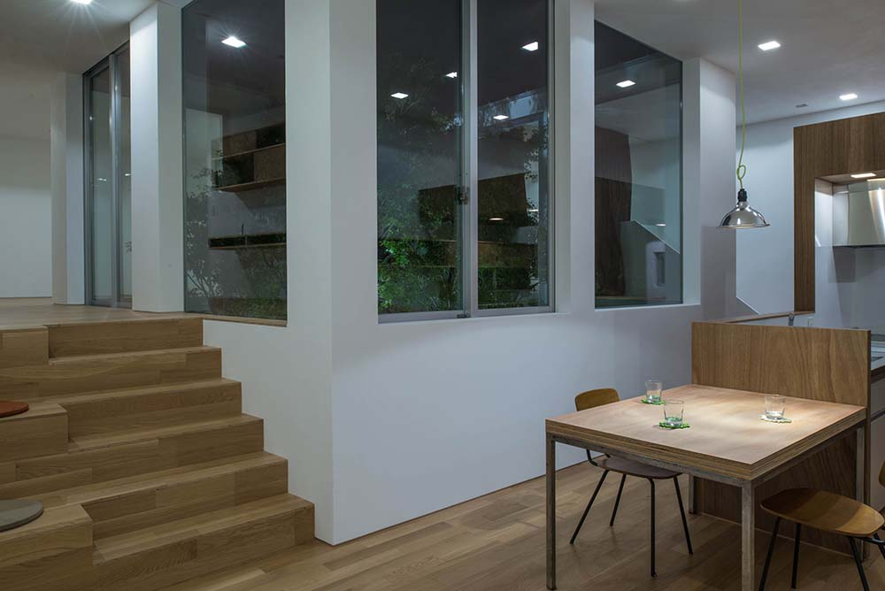 This is a look at the eat-in kitchen with a wooden attached dining table to the kitchen island.