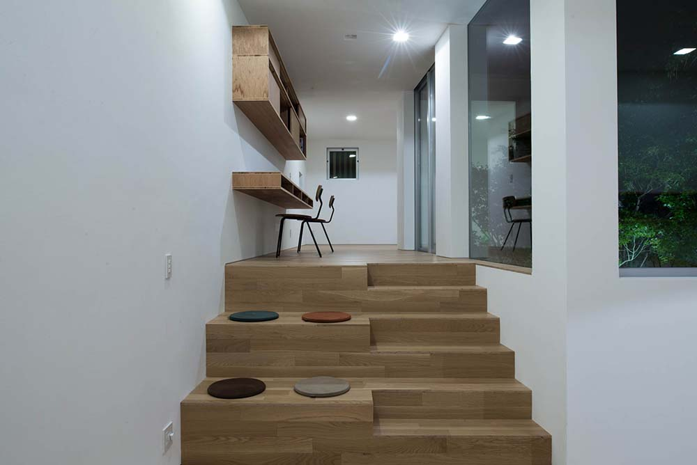 This is the home office that has an elevated area, built-in floating desk, shelves and a set of wooden steps.