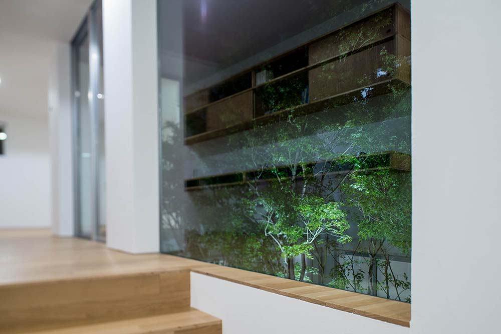 Across from the wooden floating desk and shelf of the home office is a set glass walls.