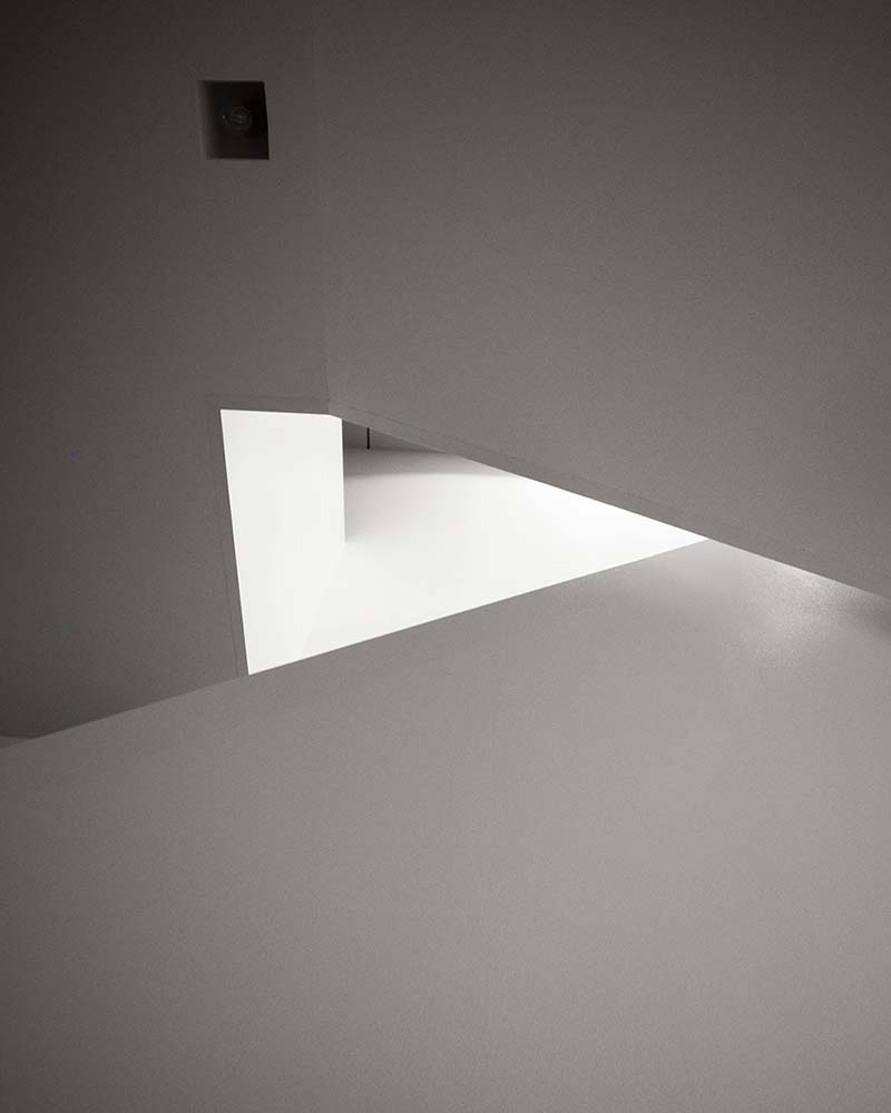 This si a look up at the staircase of the house with light beige walls and a warm glow.