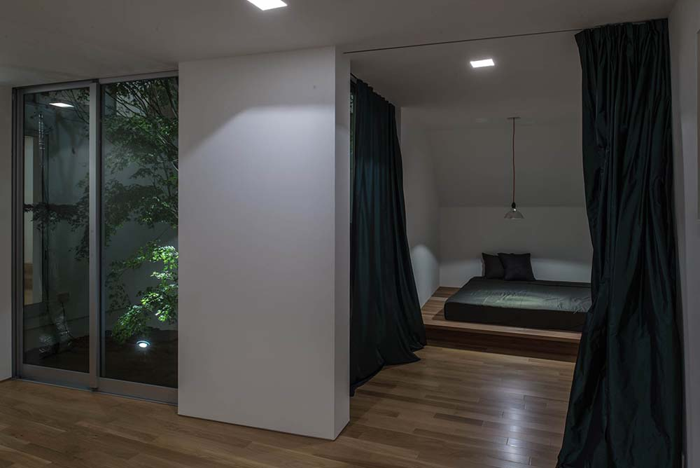 This is a look at the bedroom that has a simple low platform wooden bed that matches the hardwood flooring.