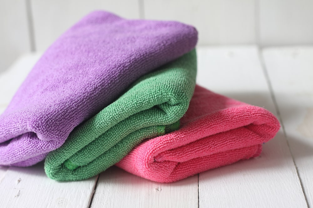 Multicolored microfiber towels stacked on a white wooden table.