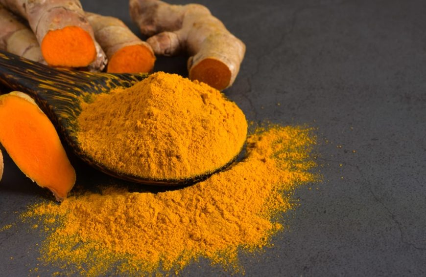 A close look at a bunch of turmeric powder along with fresh turmeric gingers.