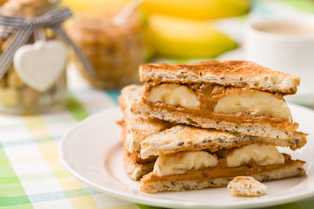 A plate of peanut butter and banana sandwiches.