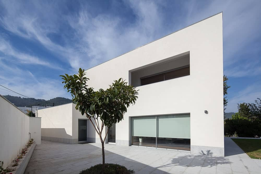 This is a view of the house exterior with simple bright beige exterior walls and structures paired with large glass walls and simple landscaping on the side.