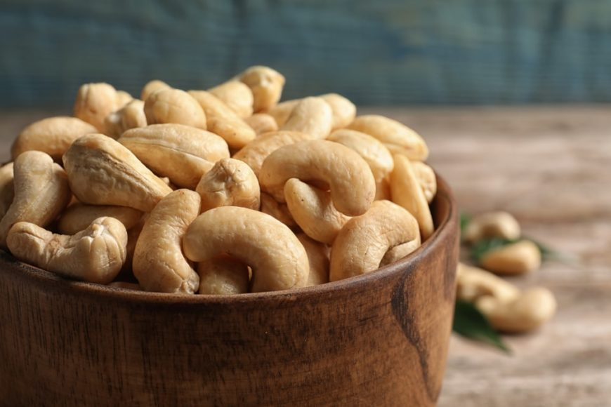 A close look at a bunch of cashew nuts in a wooden bowl.