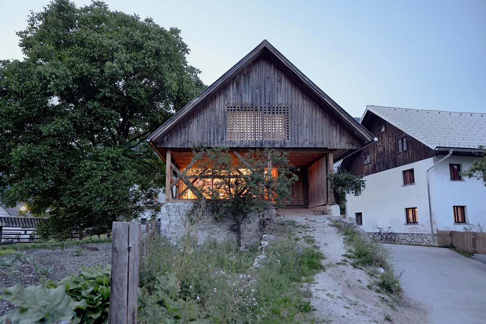 This is a look at the front of the farmhouse-style home with wooden exterior walls and A-frame roof above the main entrance that has a covered porch that glows warmly from the interior lights.
