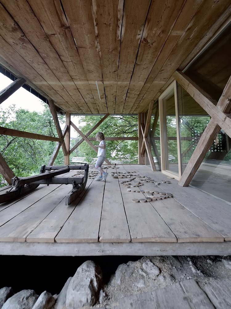 The has has a front porch with a wooden flooring to match the ceiling and the wooden beams.