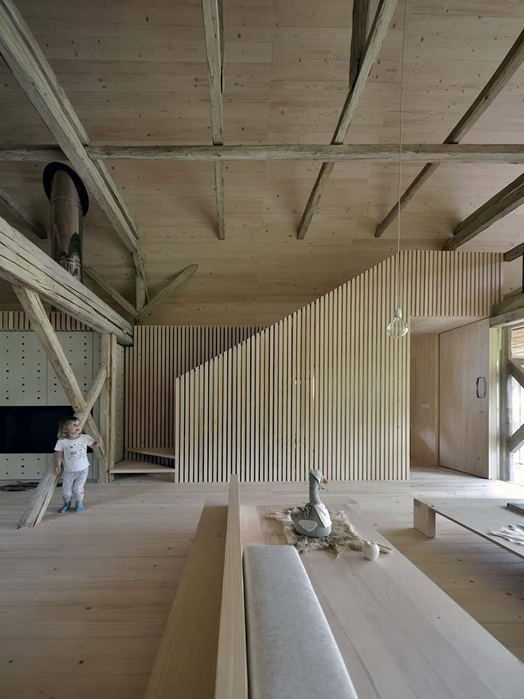 This is a close look at the wooden sofas of the living room as well as the unique staircase with slatted walls.