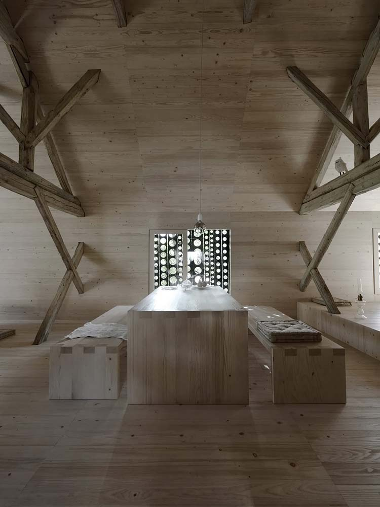 This is a full view of the dining area and its wooden dining table that is brightened by the window on the far side and adorned with exposed beams on the walls.