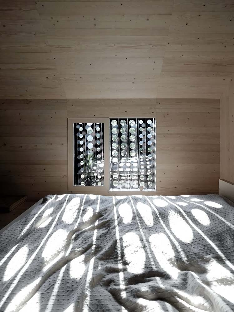 This is a closer look at the head of the dining table illuminated by the natural lighting from the patterned window.