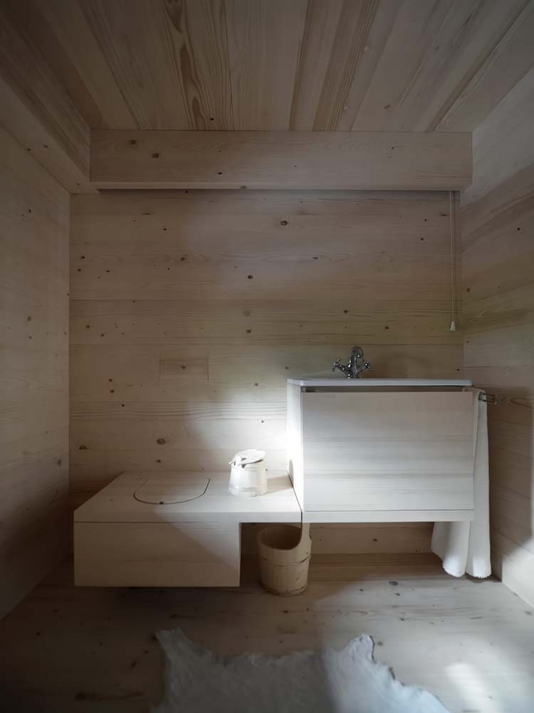 This is a close look at the bathroom with a bowl and vanity housed in one unique wooden structure.