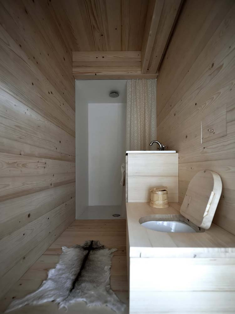 On the far side of the bathroom after the wooden structure of the sink and toilet is the shower area.
