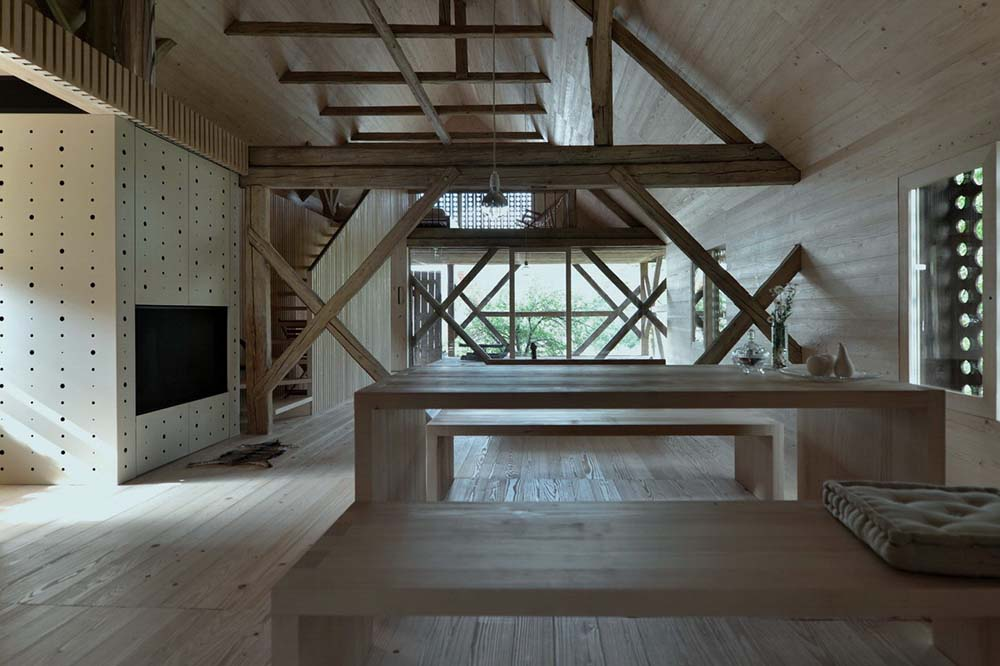 This is a view of the great room from the vantage of the dining area with a view of the fireplace by the wooden beam.