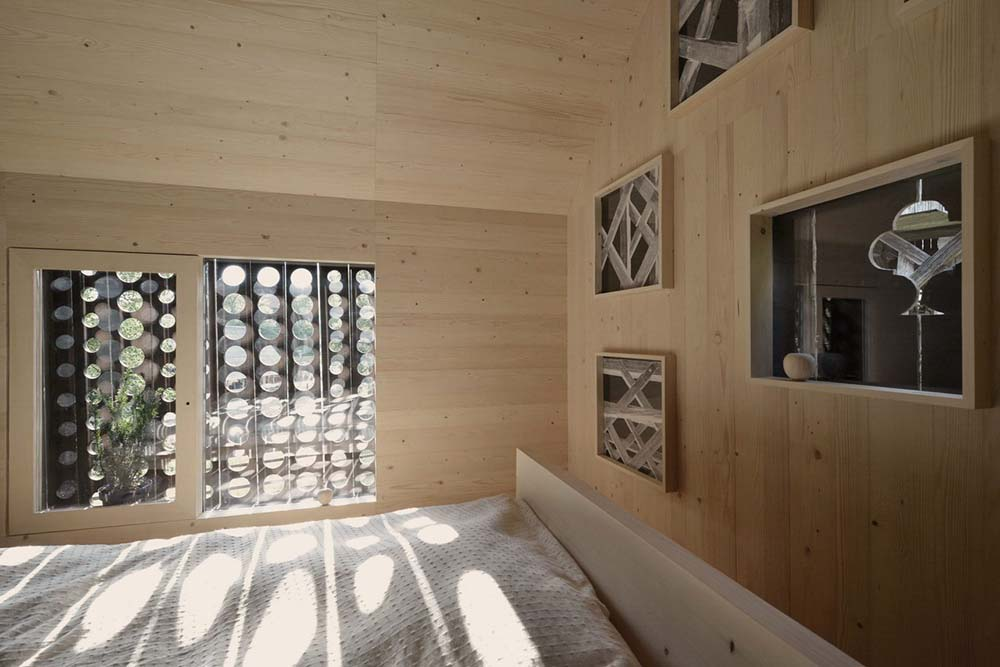 This is a closer look at the be with a wooden frame that matches perfectly with the walls and the ceiling.
