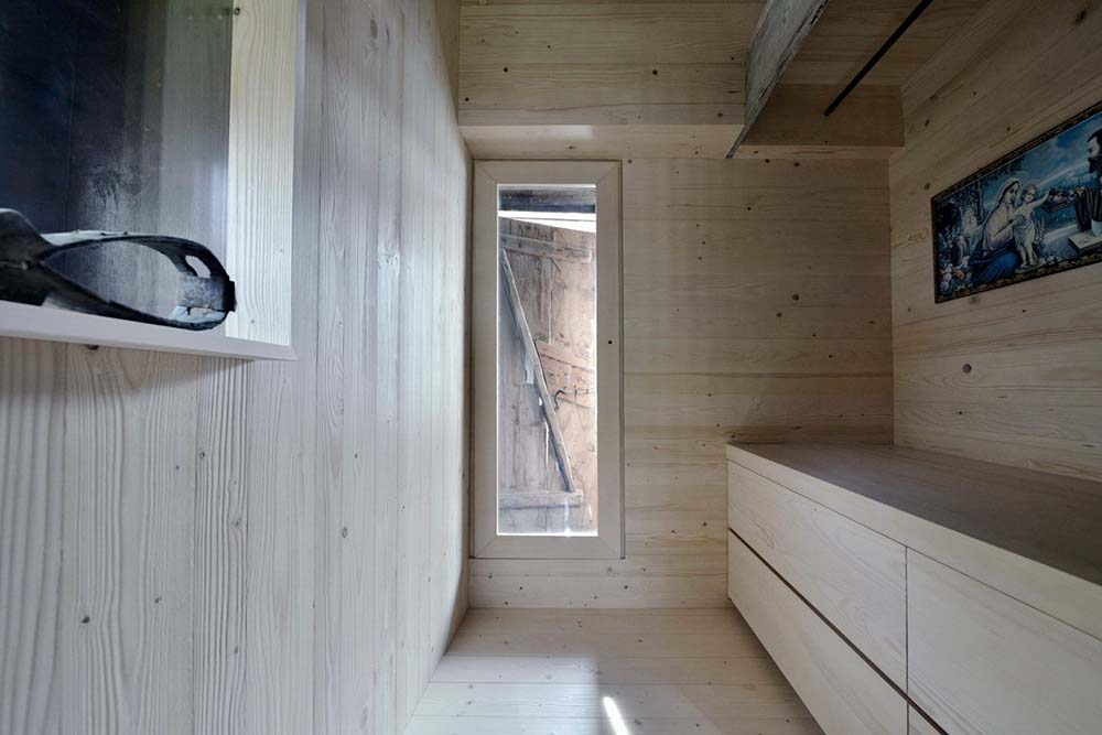 This is a narrow back exit for the house with a set of built-in wooden drawers on the side and a door on the far end.