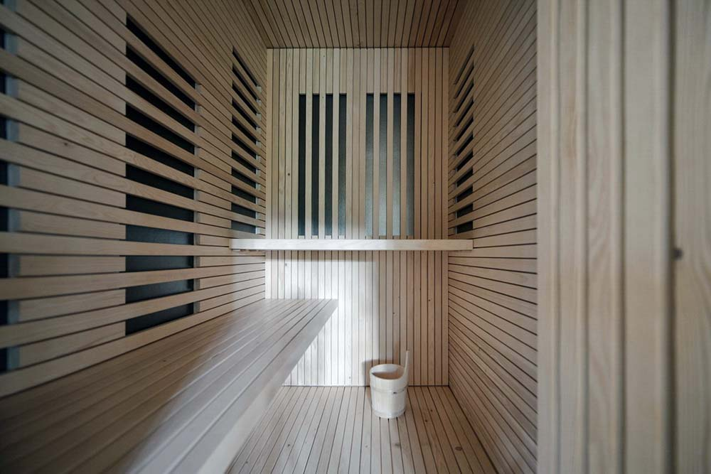 This is a close look at the sauna of the house with consistent wooden tones on its walls, built-in wooden bench and floor.